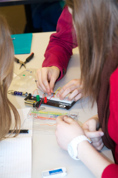 MIT students creating a simulation of the biological circuitry using breadboards.